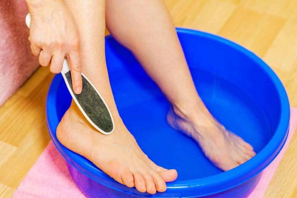 woman soaking feet in hydrogen peroxide